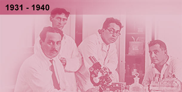 Imagem da época, esmaecida em tons sépia de reunião de pesquisadores laboratório