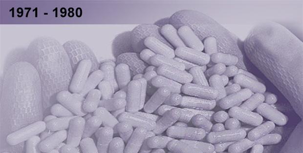 Imagem esmaecida em tons azulados de pessoa segurando várias cápsulas de remédio